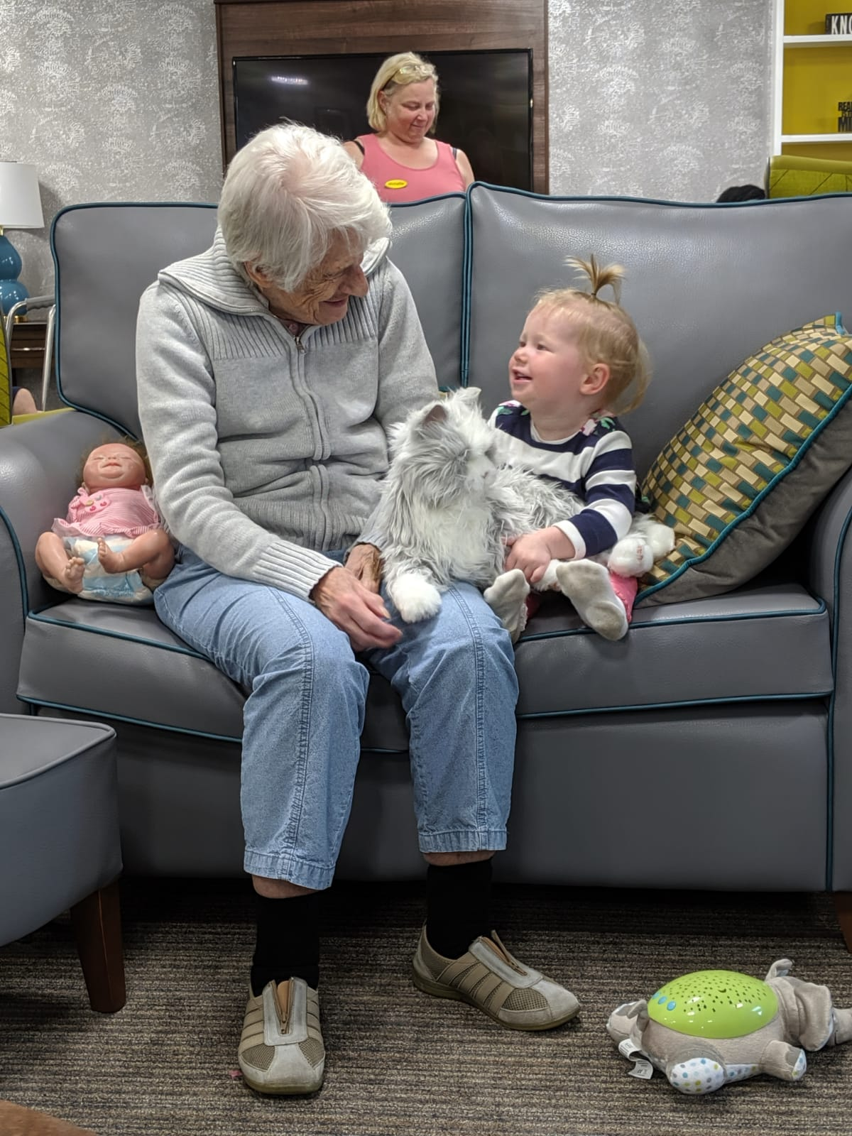 Older adult and child spending time together laughing at care home in Hucknall